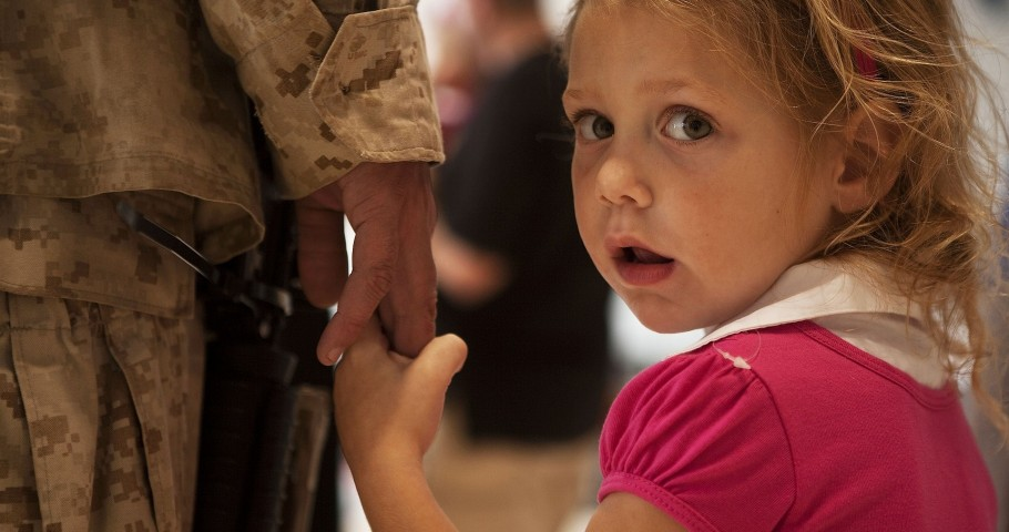 Military parent holding young daughter's hand.