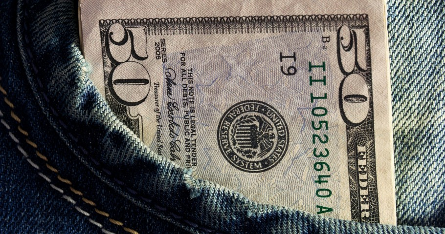 A fifty dollar bill and other cash in jeans pocket.