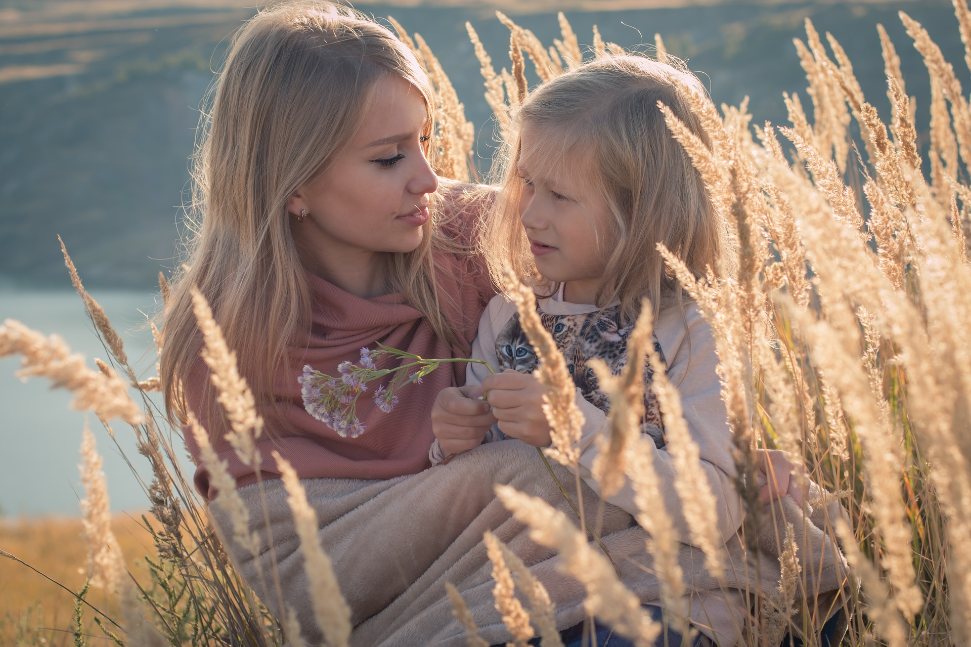 Mother and young daughter sitting in a field.