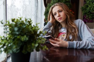 Sad young woman holding a phone.