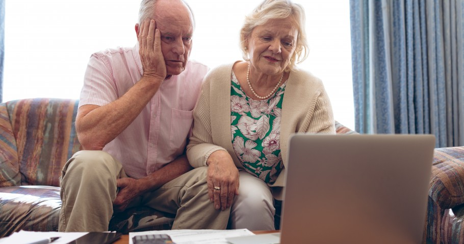 Concerned senior couple looking at laptop with phone on table.