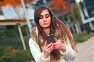 Concerned young woman looks at her cell phone.