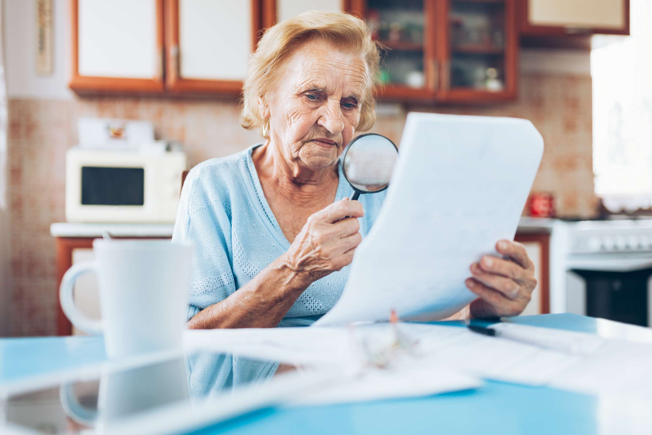 Senior woman looking at bills at the kitchen table.