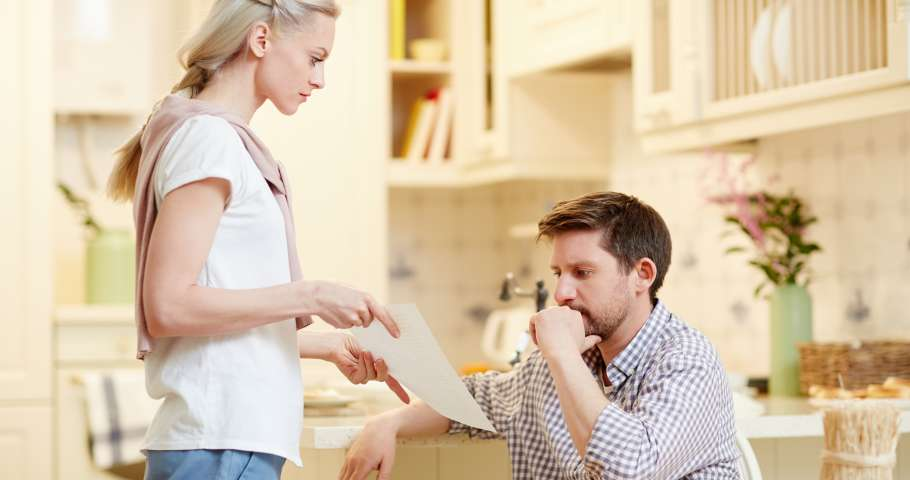 Perplexed young man looking at paper in his wife hands during talk in the kitchen
