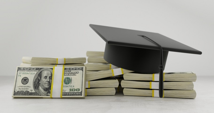 Graduation cap sits on large stacks of cash.