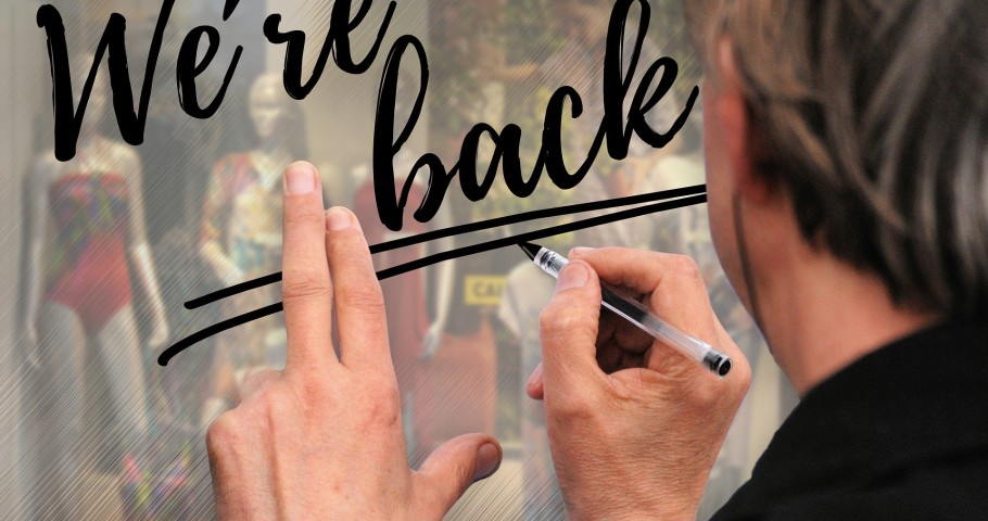 "Man writes ""We're back"" on the window of a boutique."